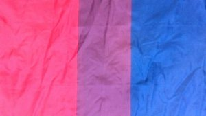 Bi flag, as slightly crumpled fabric flat on a surface. Pink, purple, blue.