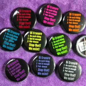 "Nine button badges each have the text ""Bi Erasure / 1 No such thing / 2 Not bi enough / 3 Put-downs / Stop that! / We exist!"" Each badge has a different colour of lettering, on a black background. They're resting on purple velour cloth. At the side of the pic is one more badge, flipped over to show the back and the pin, but half this badge is off the edge of the photo."
