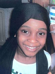 Photo of Khyra Ishaq. A young Black girl is smiling at the camera. She has baby teeth and brown eyes. She is wearing a black headscarf. She looks happy.