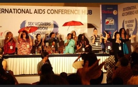 "Photo showing about 10 people on stage at a conference, plus the silhouetted backs of a few of the audience, all applauding/celebrating. (I'm guessing it was taken at the end of the conference.) Most of them are people of colour. The banner behind them reads ""International AIDS conference hub / Sex Workers' Freedom Festival""."