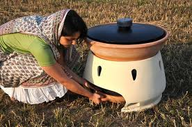 Photo of the solar oven. It looks a bit like a very big ceramic cooking pot. A woman is kneeling down to pull out the saucer-like bottom bit, where the fresh water collects.