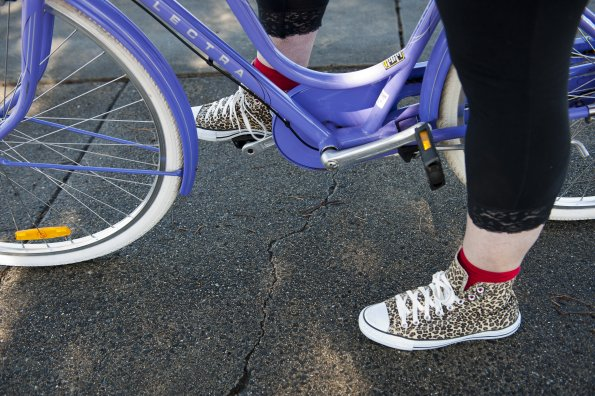 Photo: Feet, ankles and a bit of leg of someone standing across a bike frame with one foot on a pedal. The bike frame is a vivid mauve colour. The person is wearing black leggings with a lacy lower edge, red socks, and sneakers with a leopard-print pattern.