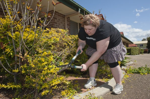 A middling-fat white woman is stooping to chop a hedge with shears. She has short fair hair with a pinkish barrette. She is wearing a black t shirt, a frilly skirt, leggings and trainers. The hedge leaves are a mix of yellowish leaves and darker green leaves. Some buildings appear in the background, including a nearby brick building which might be a house.