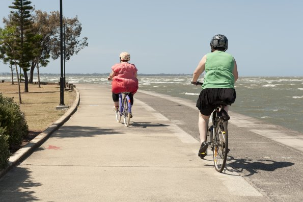 Two white people are riding bikes along a sea front on a concrete path, with the sea on their right, heading away from the camera. The first rider is wearing a red dress and is quite fat. The second rider is wearing a green top and black skirt, and isn't especially fat. Both are wearing bike helmets. On the left of the picture is a kerb and some scrubby grass and a few trees. The sky is a clear pale blue and the sea is grey with a few white waves.