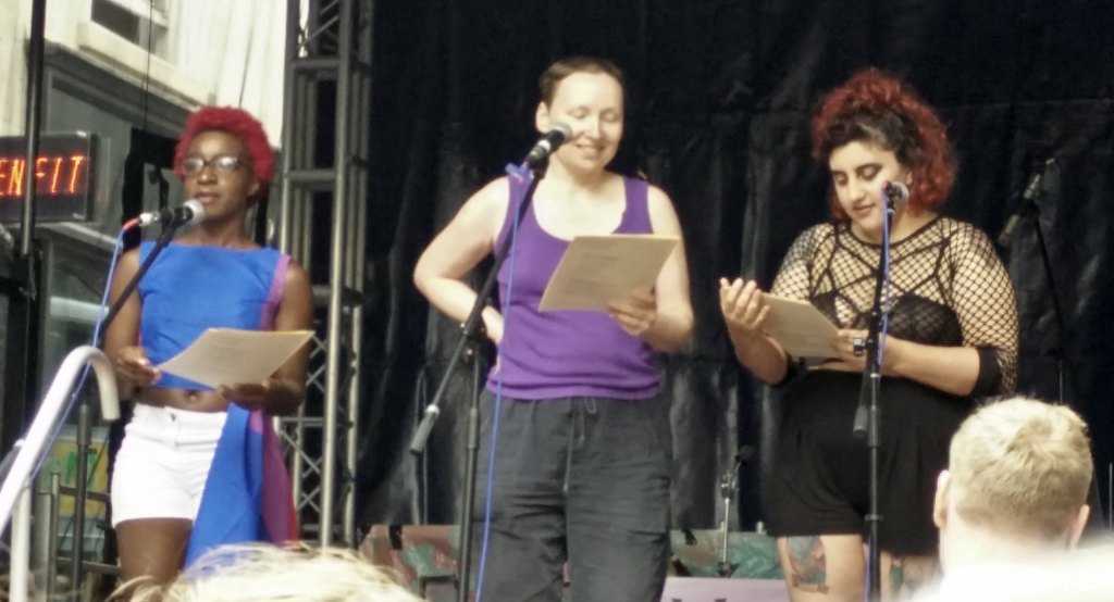 Three people on stage. Arianne, who's Black, is looking at the audience as if about to speak, and wearing a top made of a bi flag and white shorts. Jennifer and Tuk are looking down at their scripts, getting ready to speak again soon. Jennifer is white, with short hair, a purple vest top and unglamorous trousers. Tuk is a woman of colour, wearing a fishnet top and black shorts. She has curly hair tied back. All three look happy.