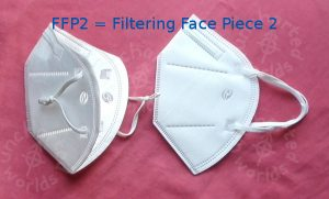 FFP2 = Filtering Face Piece 2. Two white masks with ear loops, seen from the side. The one on the right is brand new and flat. The one on the left has been opened out. Its ear loops have knots in to make them a bit tighter. Its top edge has been trimmed to be about a centimetre lower.