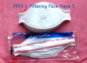 FFP3 = Filtering Face Piece 3. A shaped white mask, seen from the front. Another similar one seen from the back, still in its plastic packet, showing two rubber bands which are designed to go behind the head.