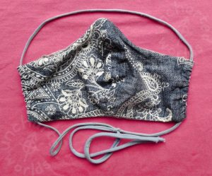 Fabric mask, quite floppy. The main fabric part has a printed pattern of line-drawn white flowers on a mid-blue background. Its headband and neck band is made of a thin curled-up strip of lighter blue stretch fabric, with a knot on the neck-band side to set its tightness.