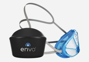 Photo of an Envo respirator. It has a partly-transparent blue plastic frame, which would cover the lower part of a person's face, and the white filter can be seen through the front grid. It has straps to go round the back of a person's head. It's shown next to a black storage case just slightly bigger than the mask.
