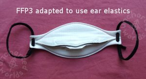 FFP3 adapted to use ear elastics. A shaped white mask seen from the angle where you'd be about to put it on, with a narrow grey foam strip across the nose area. It has black elastic ear loops.