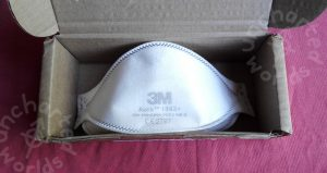 """An FFP3 respirator mask tucked into a small cardboard box. The mask is in an unflattened three-dimensional shape ready to be put on. It's white with a 3M logo in faint grey on the front, a CE mark """"CE 2797"""" and a few other numbers.."""